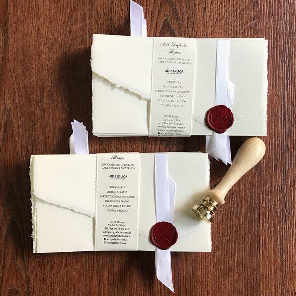 Partecipazione in carta di Amalfi con chiusura in tre parti. Dimensioni 18,5x30 cm aperta e chiusa 18,5x11 cm gr. 200 circa. La filigrana presenta lo stemma di Amalfi. Necessita del sigillo in ceralacca per la chiusura o a scelta delle Buste. Può essere spedita normalmente a mezzo posta con e senza buste. Disponibile nei colori avorio, avorio rosato, pesca, grigio perla. Dimensioni busta 11,5 x 19,5 cm 150 g/mq. Perfetta per il modello 3 ante (disponibile in colore avorio, marrone e blu) con pattina dritta e bordo pre-collato. Ceralacca rossa e nastro in raso.